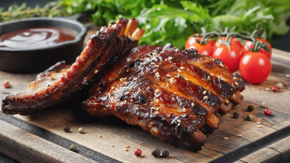 A rack of barbecue ribs on a cutting board next to some cherry tomatoes.