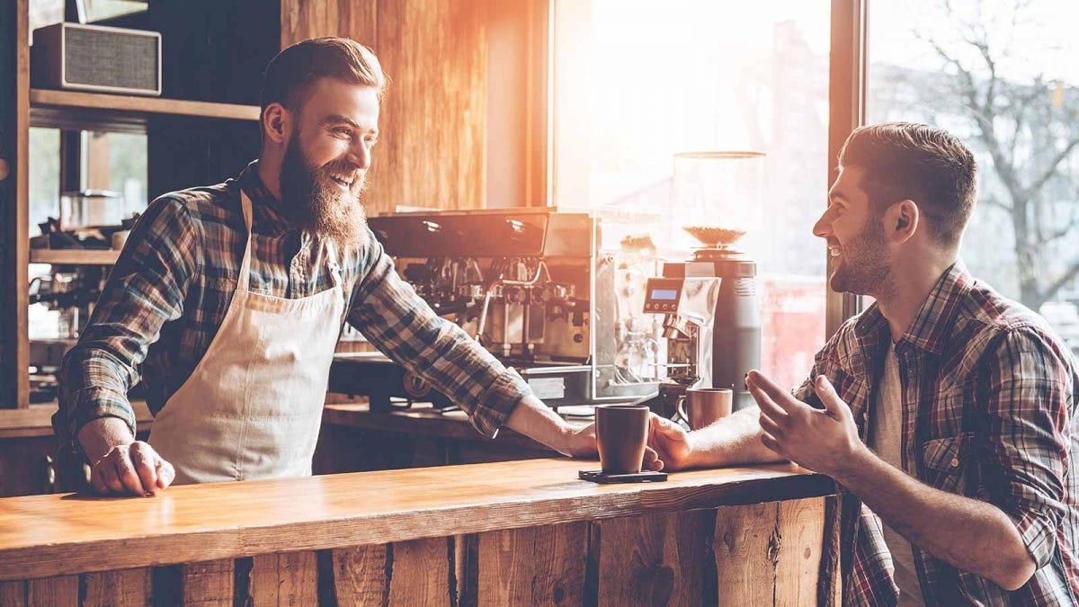 Man talking to his barista and thanking him for good service
