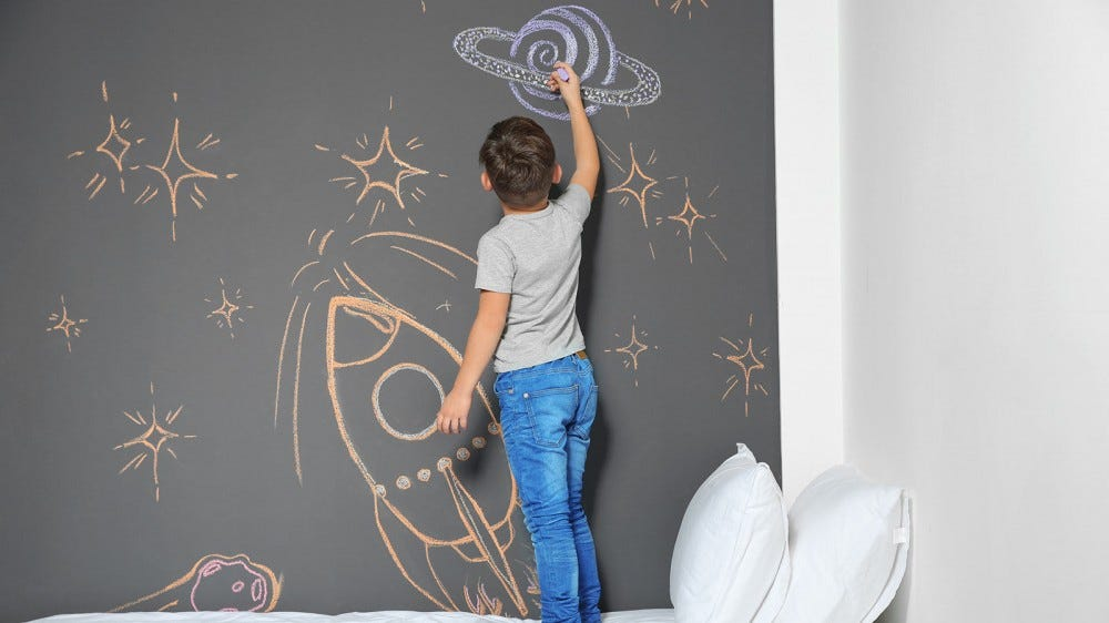 A little boy drawing a planet on the chalkboard wall in his bedroom.
