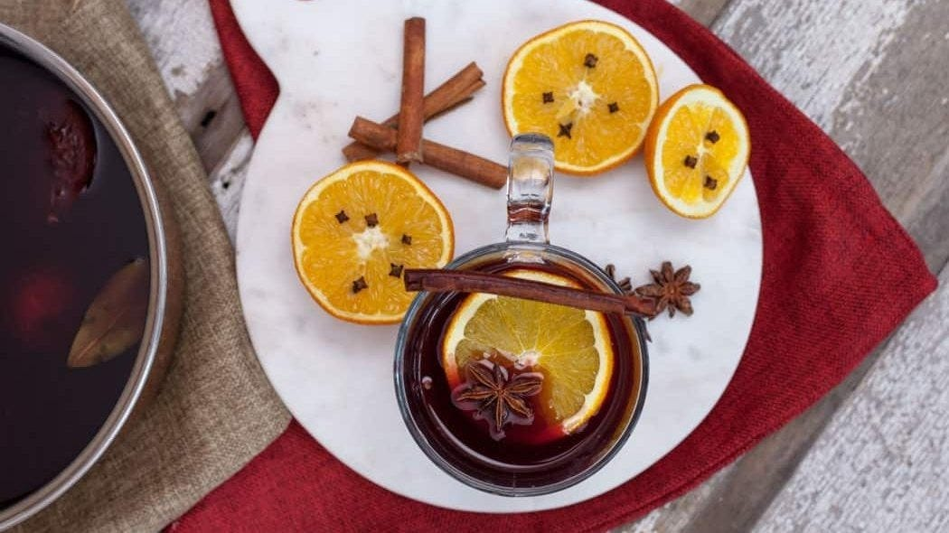A glass of Gluhwein (German Mulled Wine) with an orange slice and star anise in it, and a cinnamon stick resting over the top.
