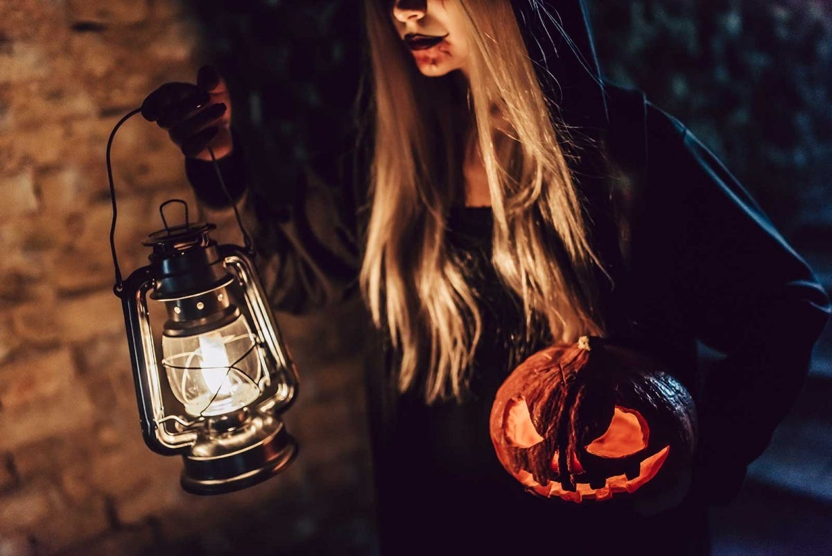 woman dressed up a as a witch carrying a lantern and pumpkin