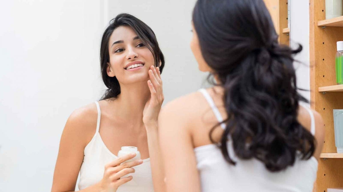Woman putting cream on her face while looking in the bathroom mirror