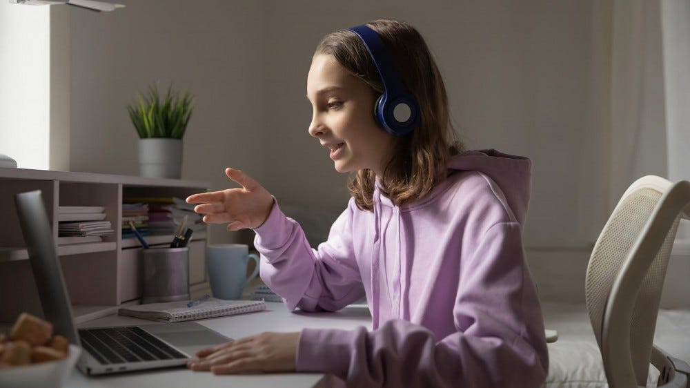 A young girl wearing headphones and tutoring someone via her laptop.