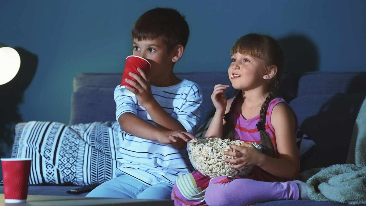 A little boy and girl sitting on a couch with a bowl of popcorn and drinks.