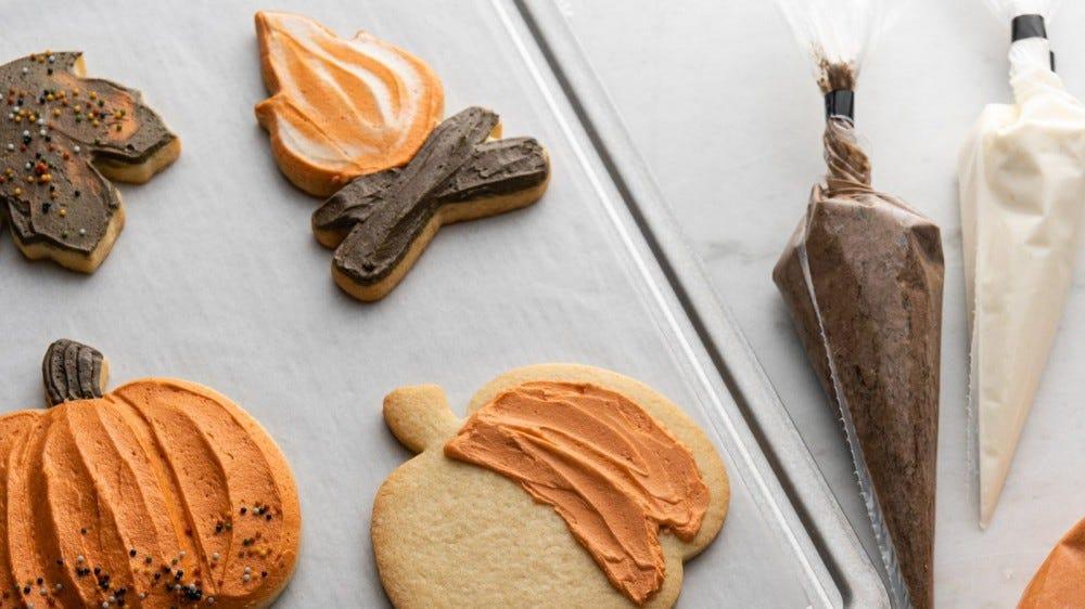 Cookies decorated with orange, white, and brown icing sit on a cookie sheet.