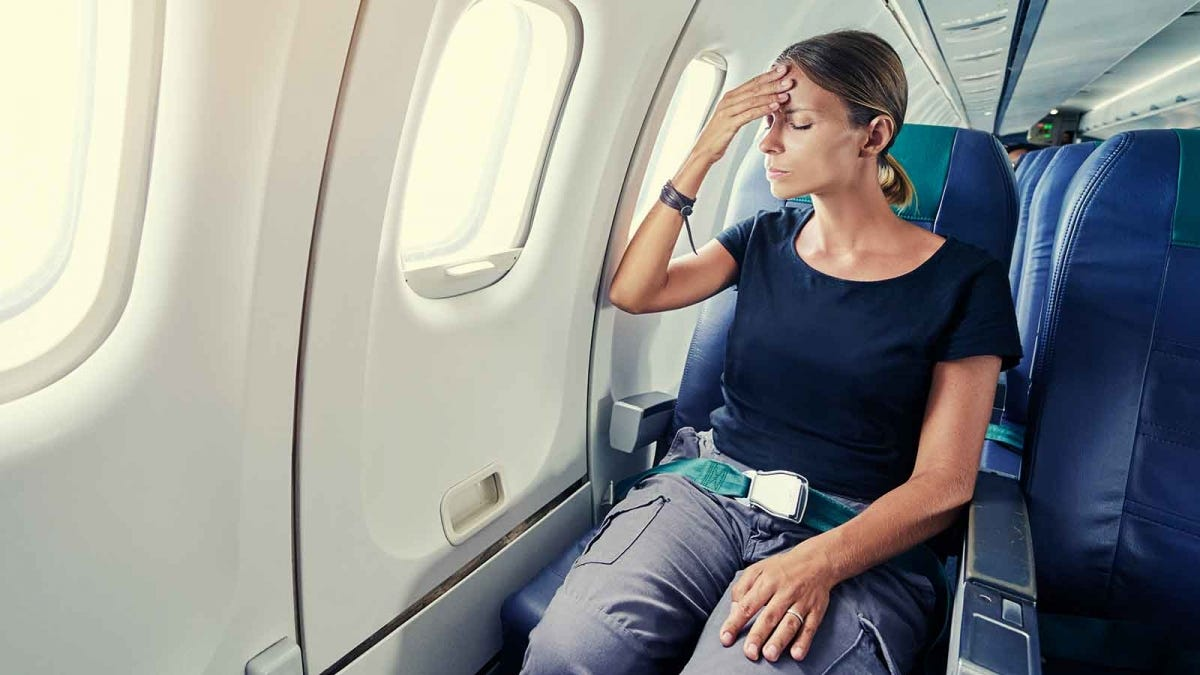 woman on an airplane, stressed about flying