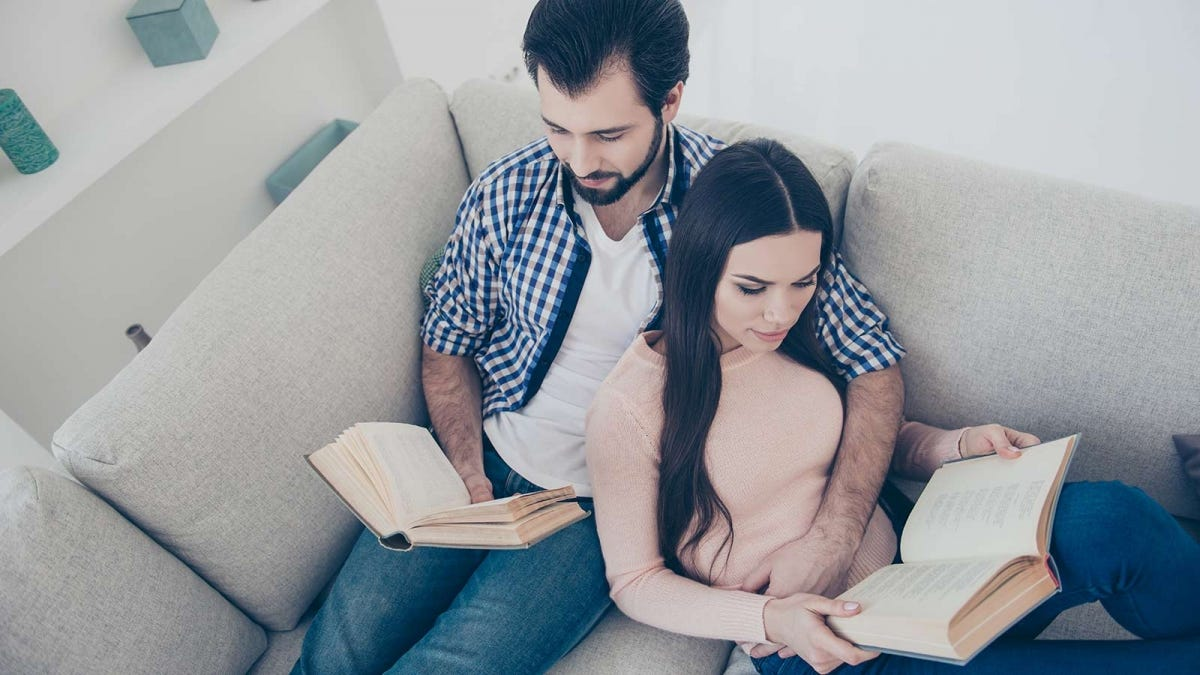 A man and woman snuggled on a sofa reading books.