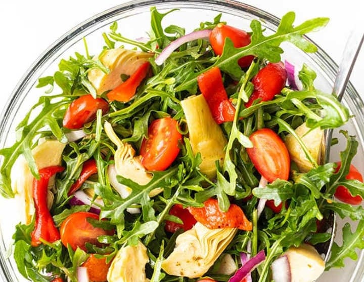 Freshly tossed arugula salad, topped with marinated artichoke hears, halved tomatoes and red onion.