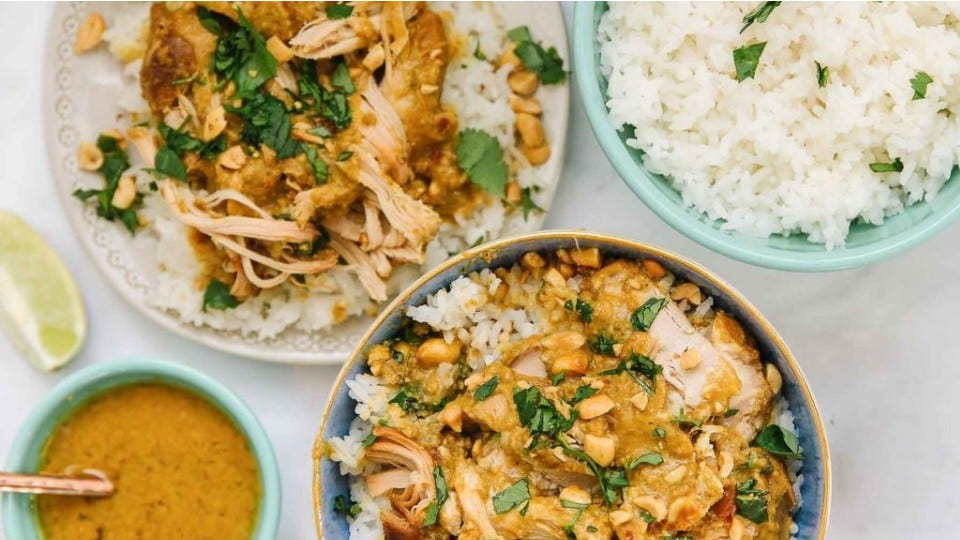 A bowl and a plate of white rice topped with hot peanut chicken satay, with a side of peanut sauce and white rice.
