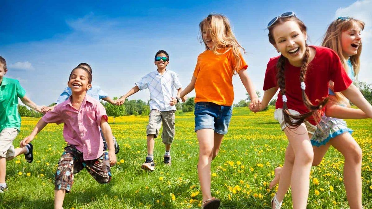 Children playing outside in a dandelion filled field