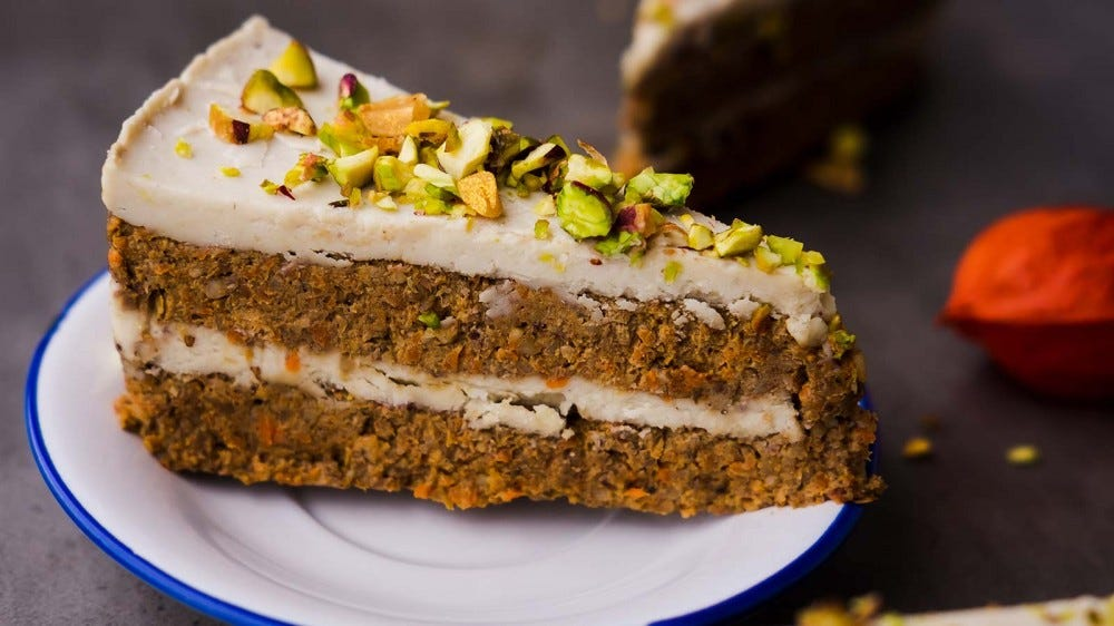 A fresh slice of vegan carrot cake, sitting on a white plate.