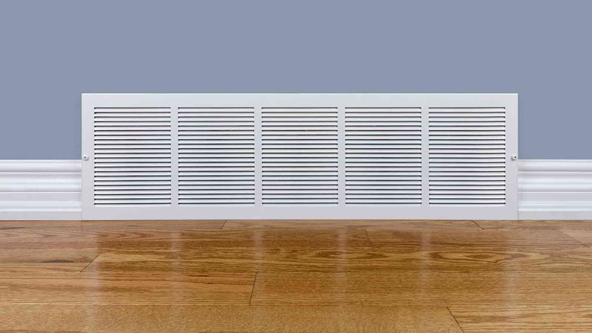A floor-level air return vent in a home with hardwood floors.