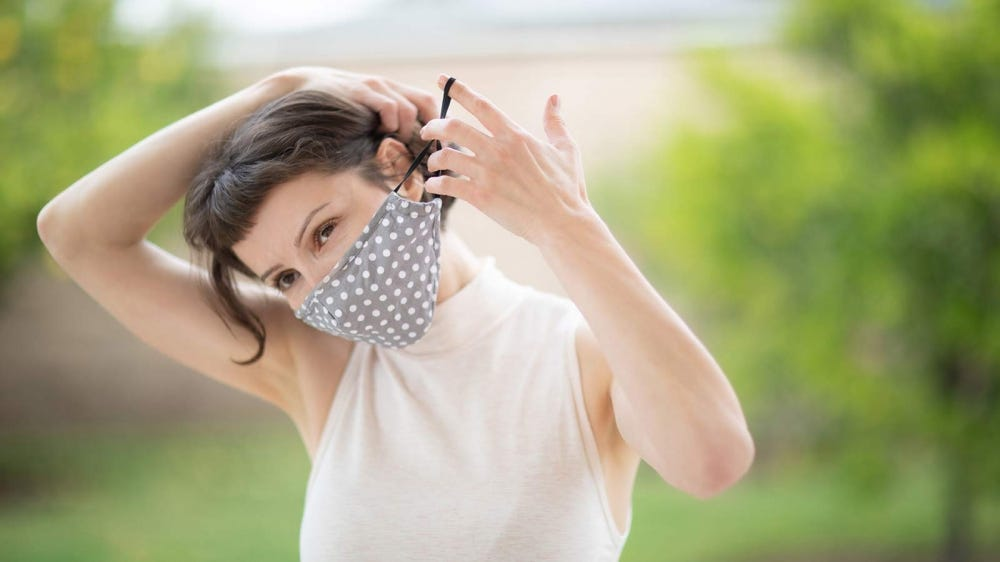 Woman putting a cloth face mask on.