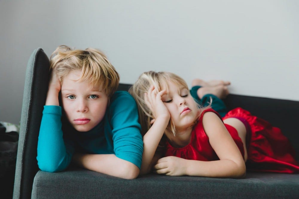 A boy and girl looking bored on a sofa.