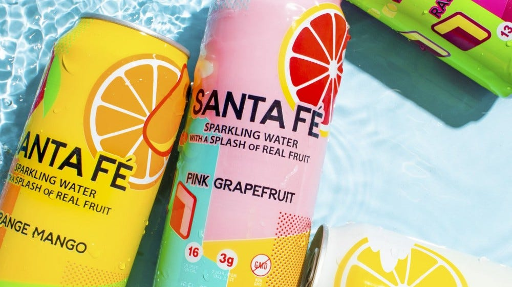 Cans of Arizona Santa Fe sparkling water sit in a pool of water.
