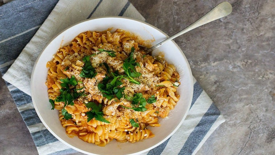 A bowl of Italian pasta with sausage topped with fresh parsley and Parmesan cheese.
