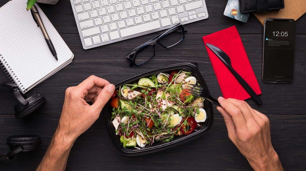 A man eating a healthy protein-rich salad at his desk.