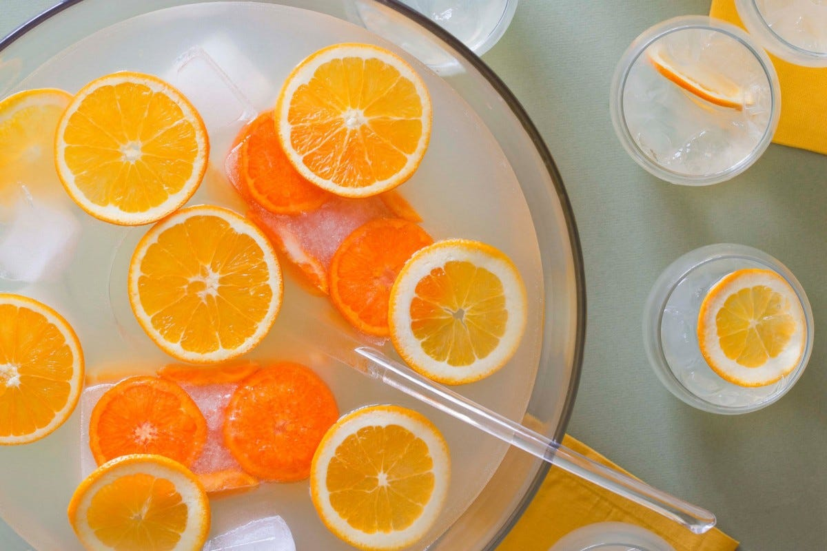 champagne citrus punch in a bowl loaded with orange slices