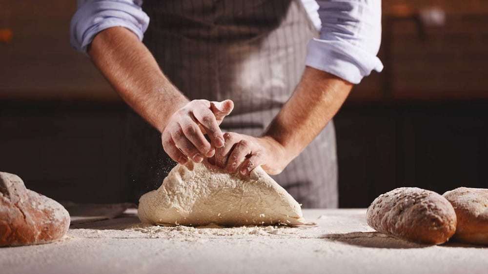 A baker kneading bread by hand, preparing it for the oven.