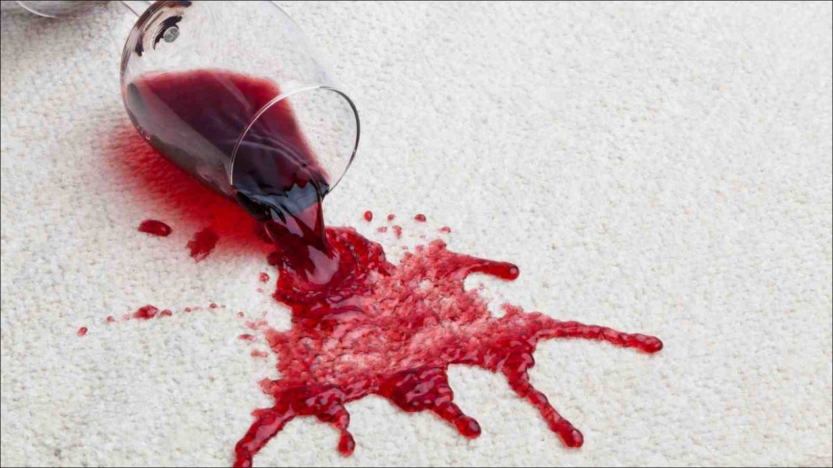 A spilled glass of red wine on white carpet