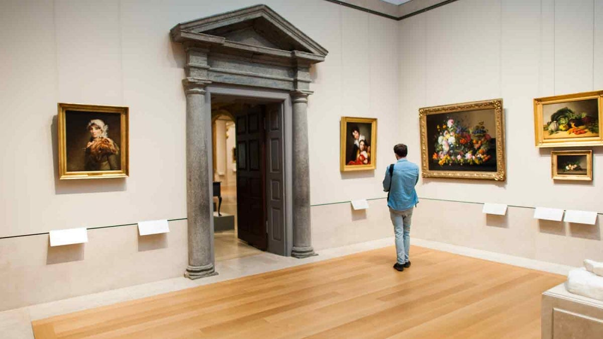 A man, all alone, studying a painting in the Metropolitan Museum of Art