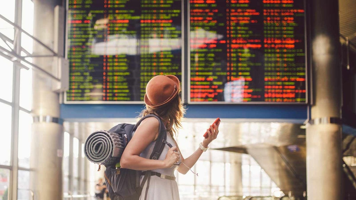 woman checking the flight schedule at an airport