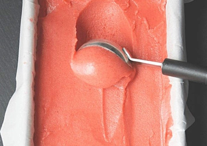 Freshly made sorbet, being scooped out of a container.