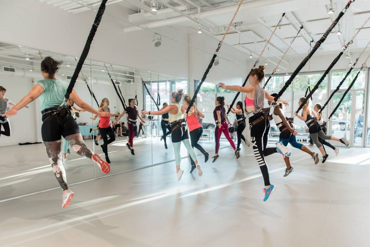 Group of women doing a bungee workout in a studio.