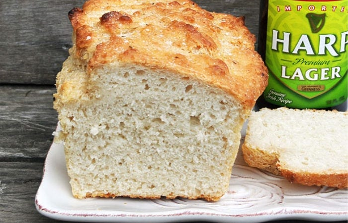 A freshly baked loaf of Irish beer bread sliced with a bottle of lager next to it.
