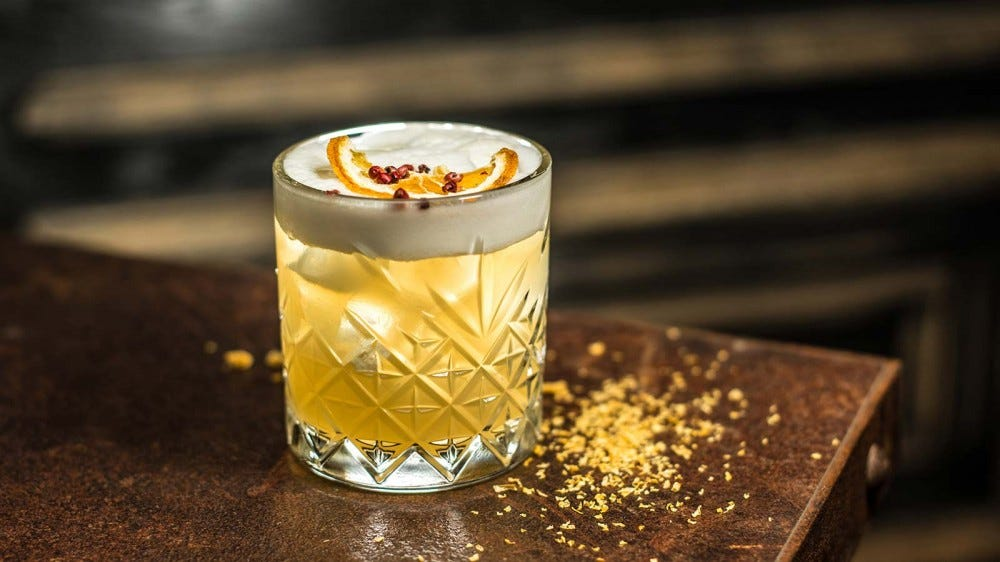 A whisky sour, sitting on a bar illuminated by lamp light.