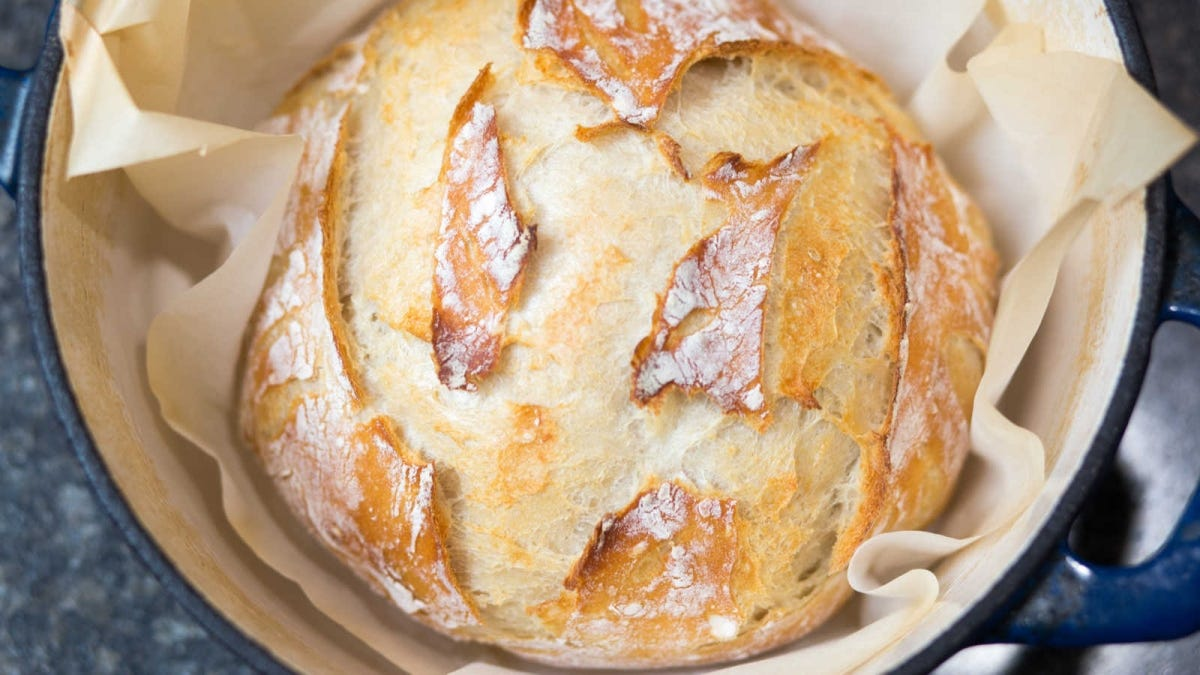 beautiful crackle crust loaf of artisan bread in a Dutch oven