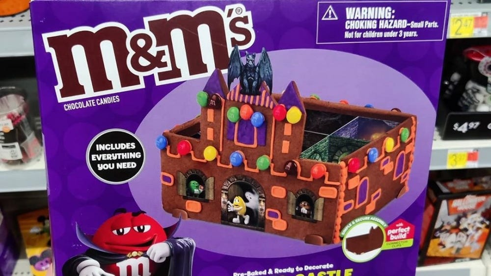 A hand holds up a box that contains pieces to build an m&m themed haunted castle.