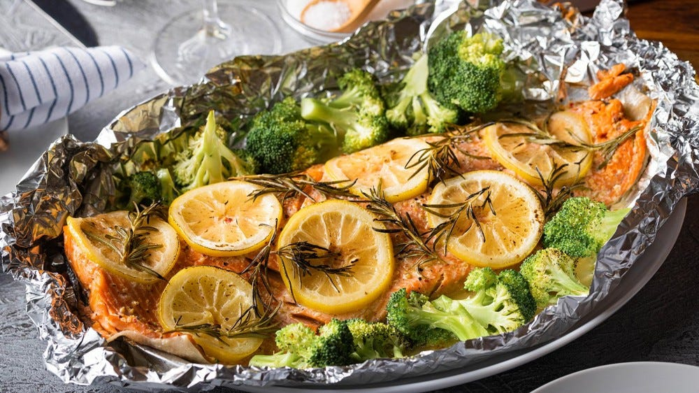 A salmon fillet seasoned with rosemary and lemon, wrapped in foil.