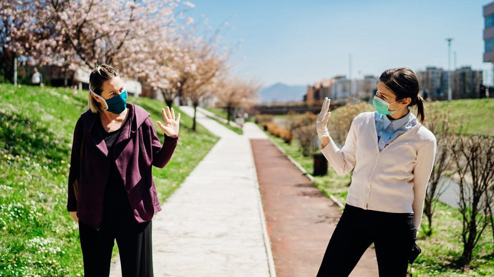 Two friends wearing masks, waving at each other as they pass on a walking path.
