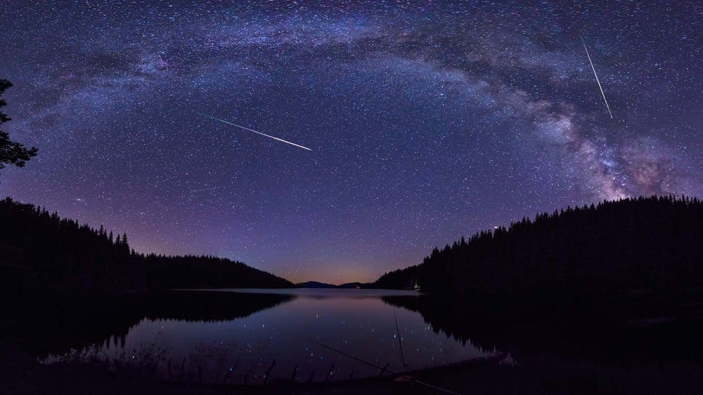 Meteors, shooting through the sky over a a scenic lake in a remote forest.