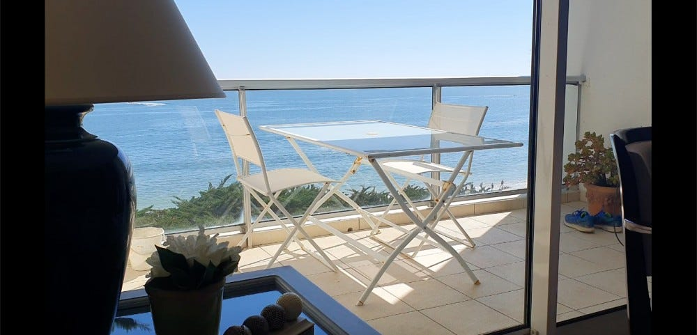 A view from a window shows the ocean and a table set on a patio.