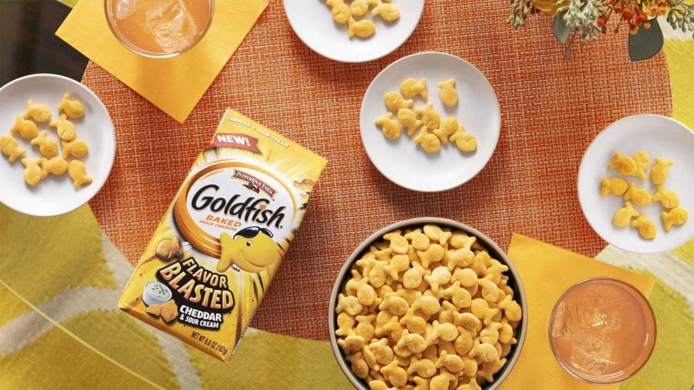 A bag of Goldfish crackers on a colorful table in a brightly decorated room.
