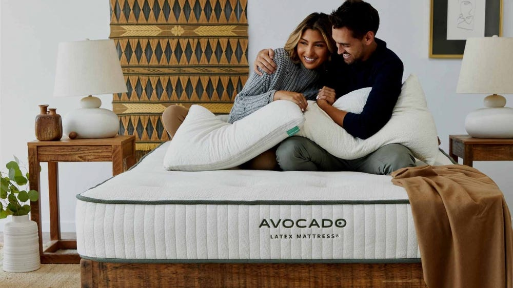 A couple sitting on a latex Avocado mattress.
