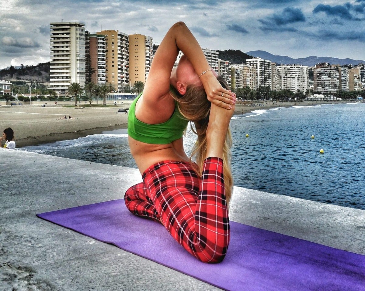 A woman doing yoga at the beach on a yoga mat.