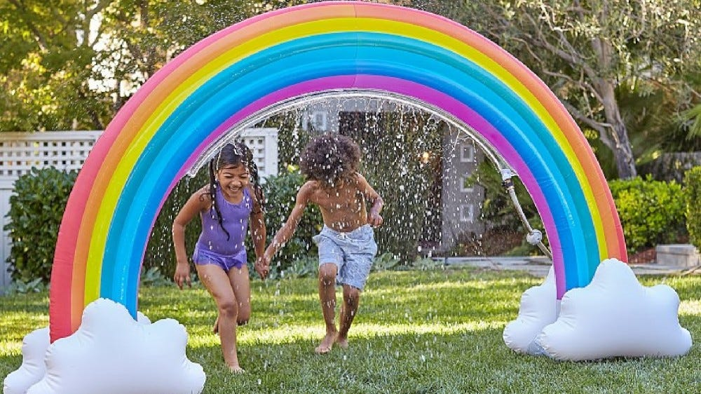 Two kids running under the Pottery Barn Kids Rainbow Inflatable Sprinkler.
