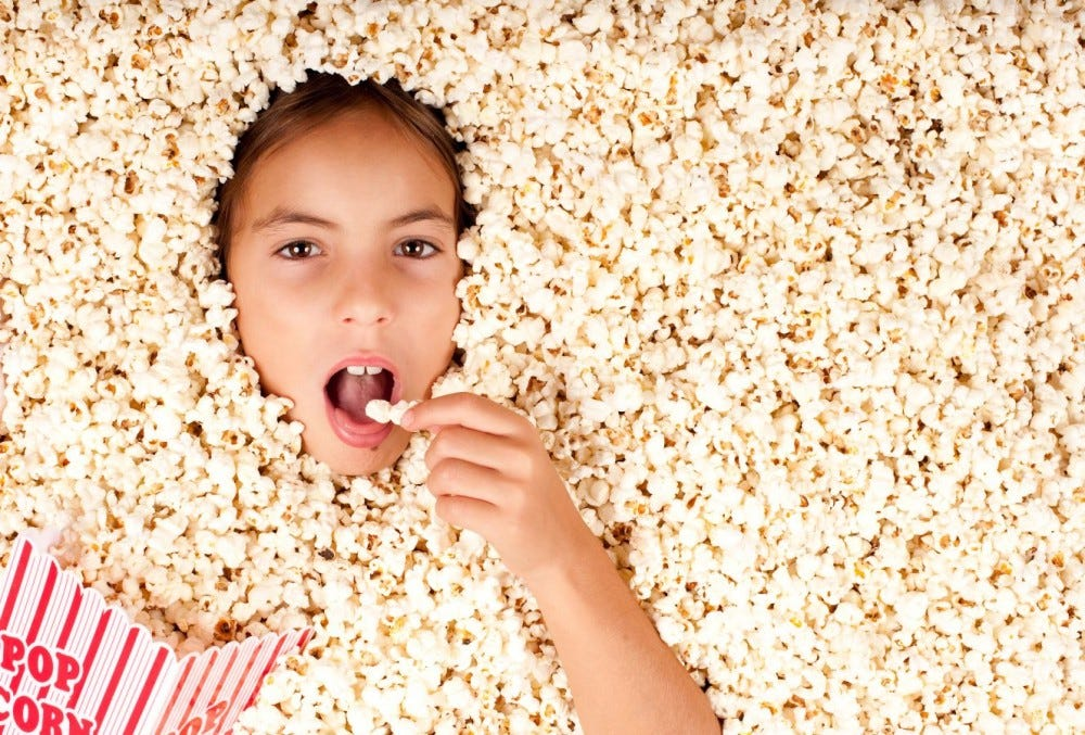 A little girl buried in and eating popcorn.