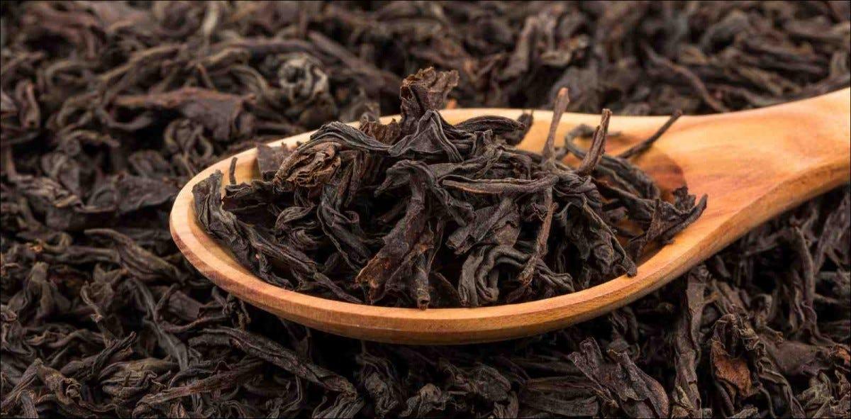 Black tea in a spoon on a black tea background