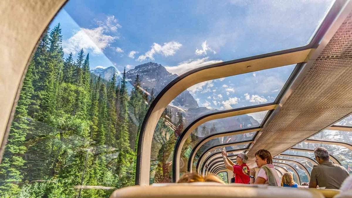 View of the Canadian Rocky Mountains through the glass roof of a dining car.