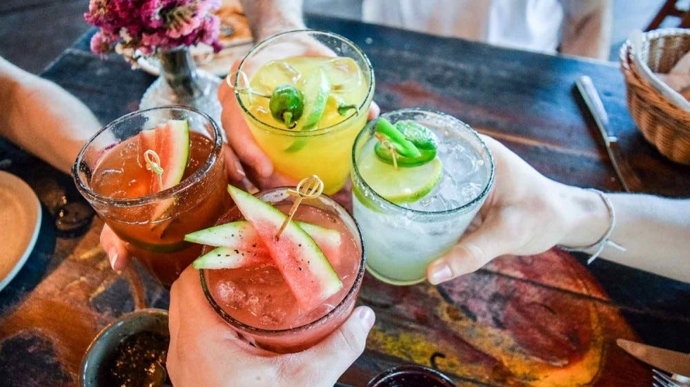 Four people cheers with multi-colored cocktails.