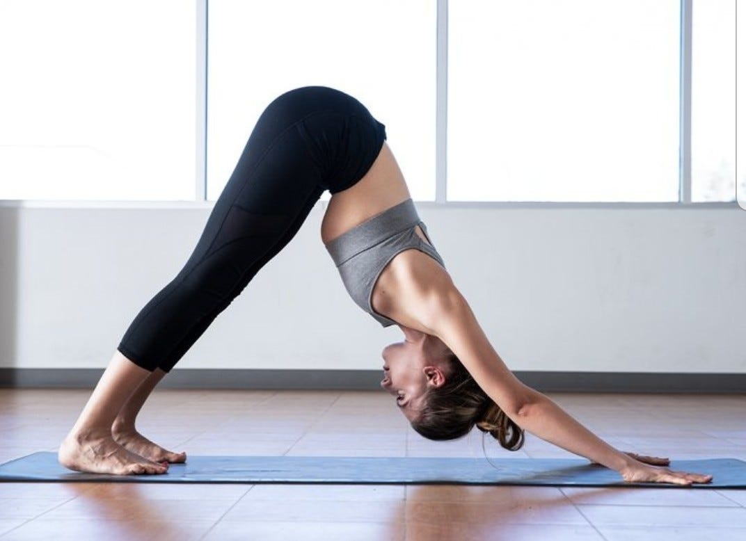 A woman on a yoga mat in the downward dog yoga position.