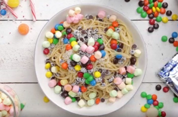 A plate full of elf spaghetti topped with marshmallows, M&M's and other candies.