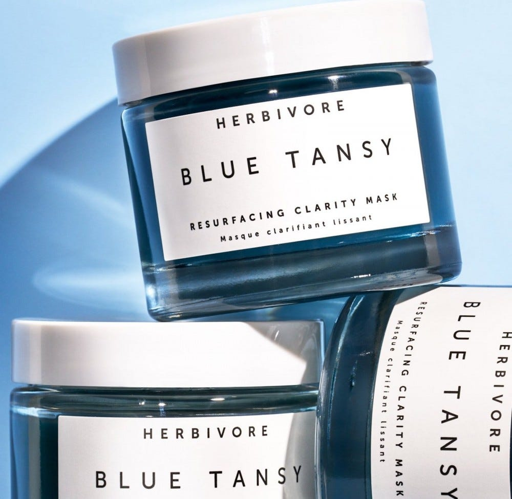Three jars of Herbivore Blue Tansy stacked on top of each other.