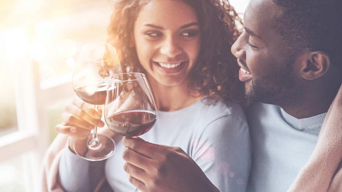 young couple toasting with a glass of red wine