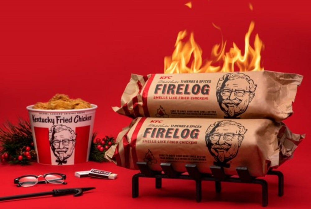 A pair of KFC firelogs sit on a grate as a faux fire burns above them, and a bucket of fried chicken sits by.