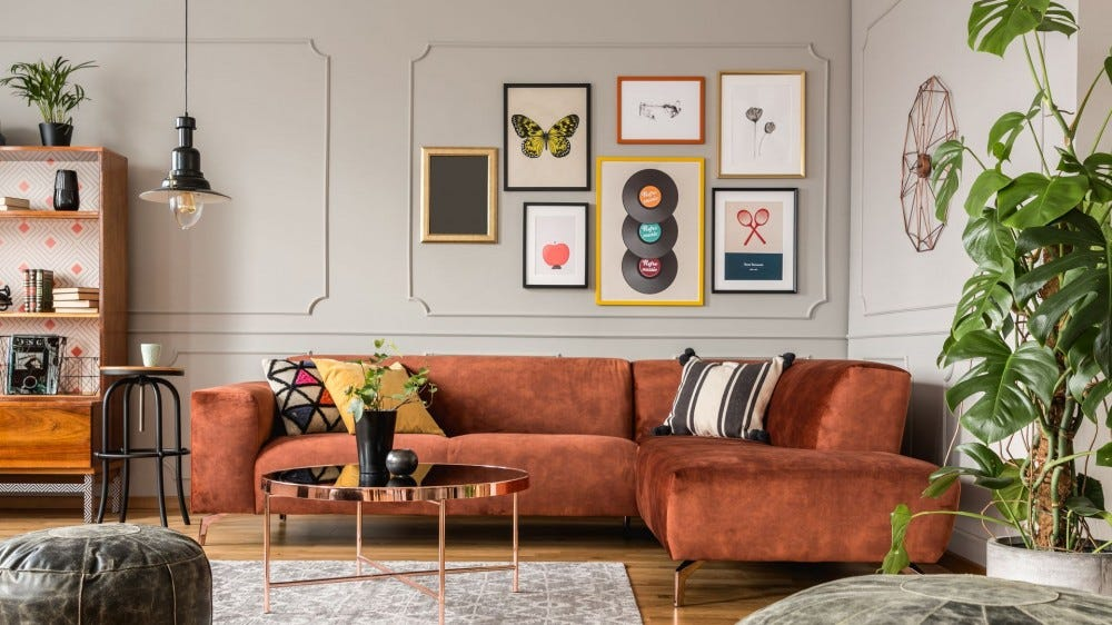 A home gallery wall featuring LP records, a butterfly, and florals in a living room.